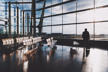 Silhouette of adult male tourist with his rolling bag standing alone in front of huge glass facade indoors of airport departure hall near empty rows of seats and waiting for his flight