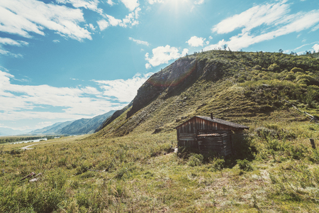 Solitary forsaken hovel on the flank of hill surround by pastures of native grasses; with mountain ridge stretching into hazy distance, river, and dirt road; Kuyus district, Altai, Russia
