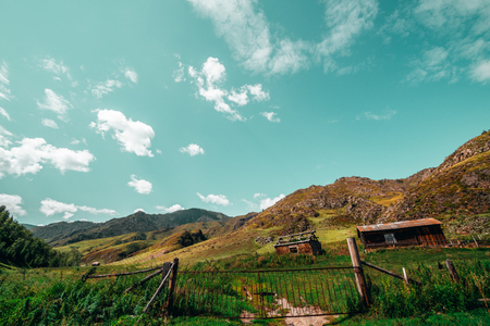 Wide-angle view of summer landscape: old metal gates with feeding ground behind, shepherds house and abandoned shack, hills range recedes into the distance; Altai mountains, Russia, Kuyus district