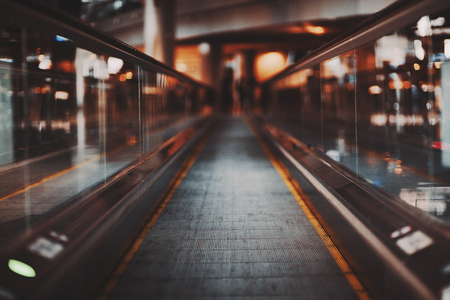 Shooting with shallow depth of field of moving walkway in modern airport terminal waiting hall; travelator trough departure area of railway station depot with multiple bokeh shapes around Foto de archivo