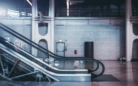 Modern partly transparent escalator in hall of subway or shopping mall, or airport terminal, or railway station depot with massive steel beams and wall in the background; moving stairway indoors Stock Photo