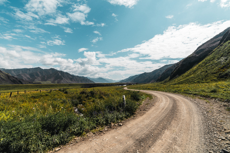 Wide-angle view of unmetalled road twisting among mountains of Altai on sunny summer day surrounded by meadows of native grasses with hills range in a distance, Russia, Kuyus district Foto de archivo