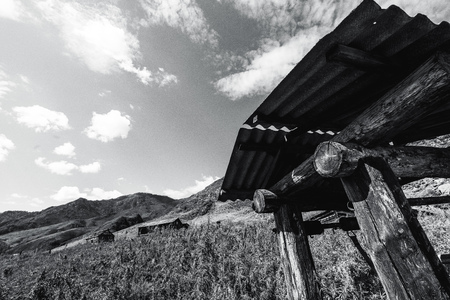 Wide-angle black and white view of old wooden abandoned draw-well in mountains with forsaken unfinished shacks in background, hill ridge, and meadow of cannabis and wormwood; copy space for your text Foto de archivo
