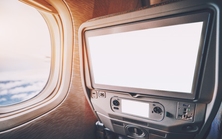 Empty white mockups of aircraft multimedia screens with remote control, close-up view of blank template of airplane monitor in passenger seat: multiple buttons and sockets, porthole on the left