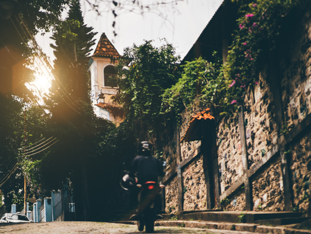 View of magical street with paving stones on the ground, small chapel in a distance, stone masonry wall with on the right, silhouette of man passing street on motorcycle, warm day in Rio de Janeiro