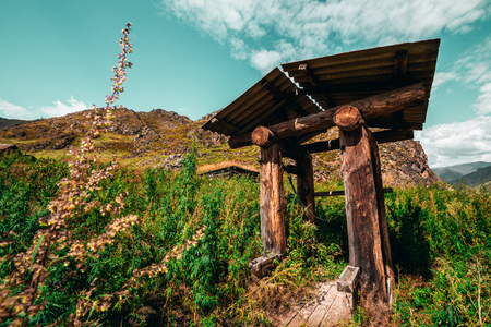 Wide-angle shooting of forsaken wooden shaft well surrounded by hills, cannabis and fleabane native grasses with ridge and valley behind; view of abandoned dug well on a summer day, Altai mountains
