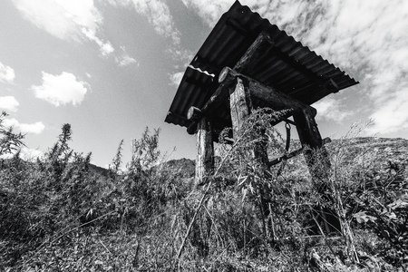 Wide-angle black and white shooting of wooden shaft well in mountains surrounded by cannabis and wormwood native grasses with hill ridge behind; greyscale view of abandoned dug well on a sunny day Foto de archivo