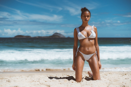 Hottie young serious African American female is standing on knees on sand of a beach with ocean, horizon, and islands in defocused background; copy space place for logo, text message or advertising Standard-Bild