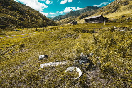 Abandoned wooden house in forsaken village surrounded by mountains, hills, and pastures; teal sky, tumbledown fence, worn through basin and leaky bucket in foreground; wide-angle shooting Banque d'images