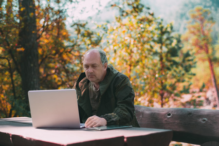 The mature confident businessman is working on his laptop with tablet pc near him on the table, while sitting on a wooden bench in an autumn forest on a sunny summer day during his vacation
