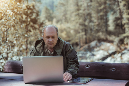 Portrait of balding mature businessman in coveralls with laptop and digital tablet sitting at wooden table during his vacation trip, with forest and hills in the defocused background; sunny autumn day Banque d'images