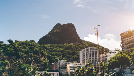 View of the Two Brothers mountain located in beach zone of Rio de Janeiro in Brazil between Leblon and Sao Conrado districts, surrounded by residential houses and hotels; sunny summer day