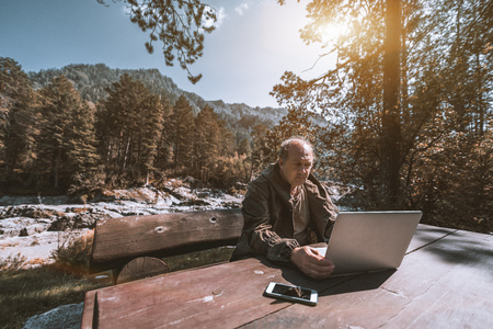 Wide-angle view of mature forester sitting alone at wooden table and working with his laptop on sunny autumn day; Caucasian aged hunter in forest near mountain river with his netbook and smartphone