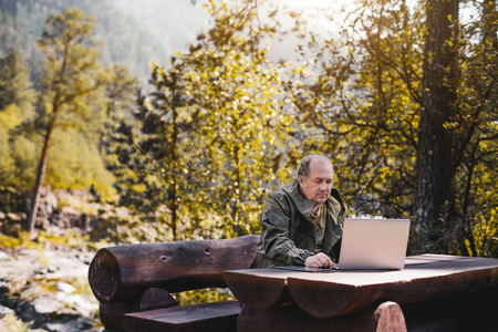 Mature man in overalls is working on laptop while sitting at the wooden table in parkland; hunter forester is sitting on the bench and using his netbook with hills and wood in the blurry background