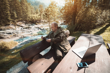 Wide-angle photo of mature forest-guard sitting on wooden bench at the table and having online conversation with his authorities via digital tablet; sunny summer day with forest and hills behind Banque d'images