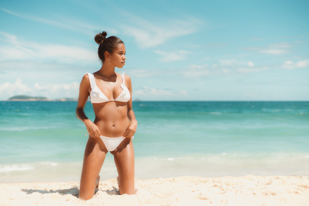 Sexy young Brazilian female on the beach looking aside while standing on knees on sand; with teal sea, horizon, island in blurry background; with copy space place for your logo or advertising message