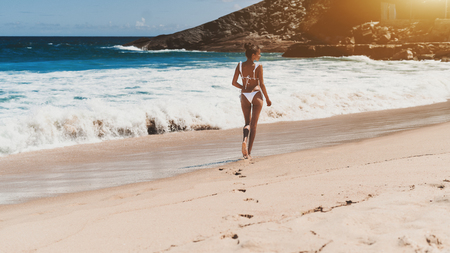 Dainty thin young Brazilian female is going away into the distance of sandy beach to the rocks in front; sexy black girl in swimsuit is walking on the ocean beach leaving footprints in the sand