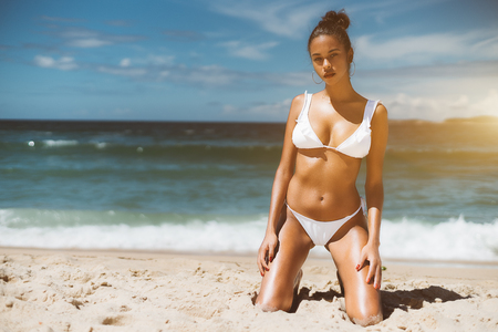 Young hot Brazilian model girl on the beach of Rio de Janeiro standing on knees on the warm sand and looking at camera, with copy space zone for your logo, advertising content or text message