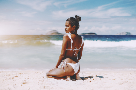 Hottie young African American female model is sitting on the sand half-turned to camera in front of ocean; rear view of foxy Brazilian girl sitting on the beach of warm summer sea with horizon behind