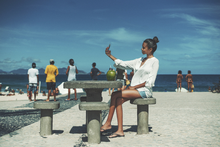 Young cute Brazilian female in white chemise is taking selfie using her cell phone while sitting on at the concrete table on embankment area next to beach with multiple silhouettes of people behind