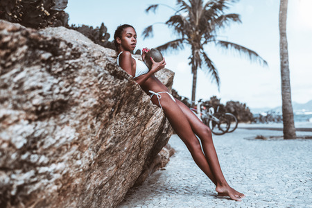 Haughty young sexy Brazilian female is drinking fresh coconut water while leaning on the crag with beach and palms behind; hot Black girl in swimsuit is quenching her thirst with coco water near cliff