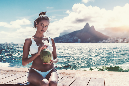 Portrait of serious hottie Brazilian girl sitting on the embankment bench and holding fresh opened coconut for drinking; with cityscape, bay, and Rio de Janeiro mountains the Two Brothers behind her Stock Photo