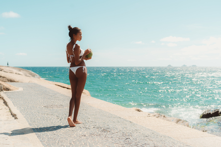 Rear view of sexy Brazilian girl with slim model body standing on paving stone near ocean beach, half-turned to the camera and pensively looking aside, holding in hands fresh coconut with straw Stock Photo