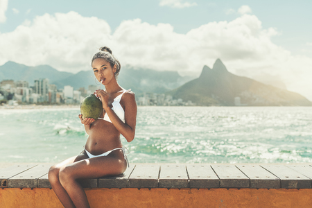Young sexy Afro American girl sitting on beach bench and drinking coconut water from fresh green coco with sityscape and hills behind and copy space place for advertising messages, your logo or text