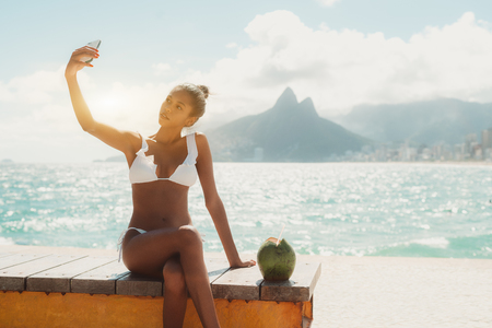 Young sexy Brazilian mulatto model girl is sitting on the bench near on the beach and taking selfie on smartphone camera, with opened green coconut near and copy space place for advertising message Standard-Bild