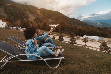 Two beautiful laughing girls (African American and Caucasian ones) on daybeds on the autumn glade are holding flying drone while it filming them; with mountains ridge in the background; autumn evening