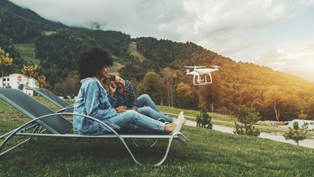 Two charming female vlogger friends of different races are sitting on deck chairs on lawn and recording broadcast using the flying modern drone in front of them, with hills in the background Standard-Bild