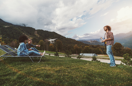 Curly bearded male hipster is capturing on video using the drone and remote controller two beautiful girls of different races for their vlog while they sitting on deck chairs on summer meadow Stok Fotoğraf