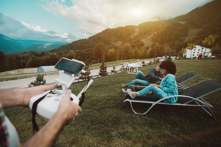 Two beautiful playful girls are recording a video for their vlog while sitting on recliners on the meadow with mountains behind; with male hands controlling flying drone in defocused foreground