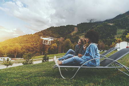 Two charming cheerful girls of different races on deck chairs on the lane are sitting to the camera of the flying drone while it filming them; with hill ridge in the background; autumn morning Banco de Imagens
