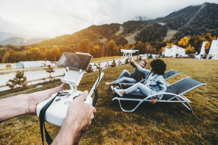 Male hands in foreground holding the remote controller for flying drone operation and two girls in the defocused background laying on deck chairs and touching this multicopter while it filming them