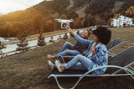 Two beautiful laughing girls (the black one and Caucasian one) are holding flying drone which is shooting video, they are sitting on recliners on autumn glade with mountains and road in the background