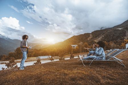 Weitwinkelansicht der Gruppe von Personen, die mit Multirotor einen Film in den Bergen dreht: männlicher Bediener steuert die Drohne, zwei lachende Mädchen auf Liegestühlen posieren vor der Kamera des Quadcopters