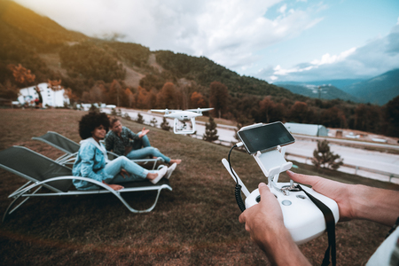 Group of people making a film using drone: male hands in foreground operating multirotor with remote controller and connected smartphone, black and Caucasian girl in defocused foreground posing to cam Standard-Bild