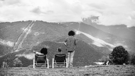 Black and white silhouettes of the group of three people on the bent: two girls are chilling on recliners, the curly guy standing next to them, the drone on the ground; mountain landscape in front