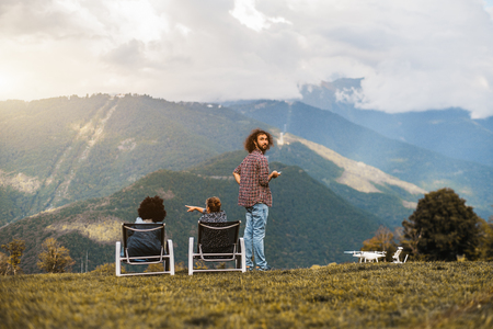 Rear view of three friends chilling in the meadow after drone filming: curly bearded guy half-turned to the camera, white girl pointing on the mountains and the black girl, both are sitting on daybeds