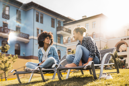 Black girl with curly Afro hair is having a chat with her female smiling Caucasian friend while both sitting on deck chairs on the green fresh lawn between modern houses on a spring sunny day Banque d'images