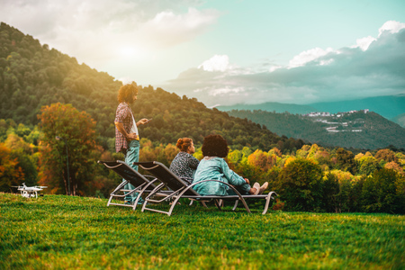 Group of three friends: two girls are chilling on daybeds on the lawn and one bearded man standing next to them and using his smartphone; drone on the ground near, colorful beautiful autumn landscape