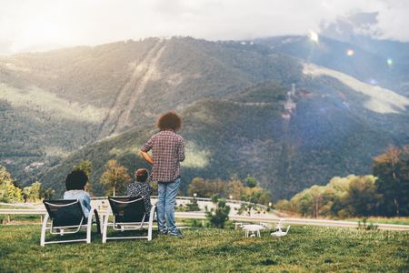 View from behind of group of three people observing summer mountains scenery from the high point: two girls of different races and the curly guy, drone on the ground near them after video shooting Standard-Bild