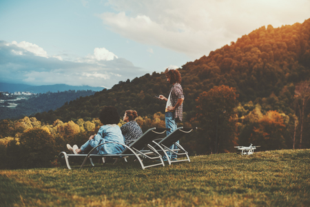 Autumn scenery with the group of three friends of different races and gender chilling on the flank of the hill and enjoying landscape view from a high point after filming a video using the drone Banque d'images