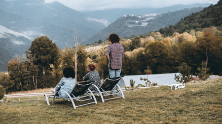 Rear view of the group of three people on the hill enjoying autumn landscape from high point of lookout: two girls are sitting on daybeds, the curly guy standing, the drone is laying on the ground