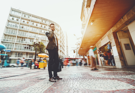 Wide-angle shooting of bearded handsome businessman in glasses and elegant formal suit, standing in center of city street with a lot of people walking around and having conversation using smartphone