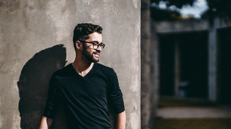 Portrait of smiling calm bearded hipster in glasses looking aside while standing in front of concrete wall outdoors on sunny day, strong shadow; with copy space zone for your advertising text or logo Standard-Bild