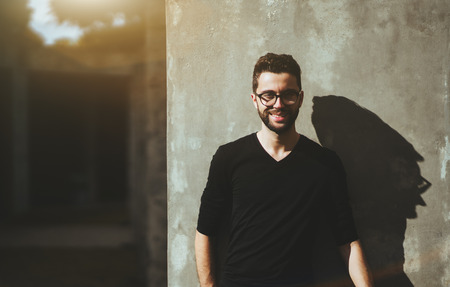 Portrait of the young smiling bearded man with the neat haircut and in glasses, standing near the concrete wall with strong shadow on it repeating features Banque d'images