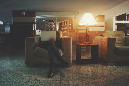 Young handsome bearded businessman in business suit and glasses is sitting in the armchair with the laptop in the dark interior of his office lobby near lamp and checking e-mail before future meeting