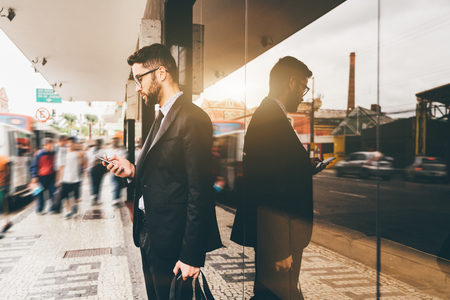 Handsome serious young man entrepreneur with beard and in glasses is answering chat message on his smartphone while standing next to mirror facade on a fussy city street next to bus stop and waiting